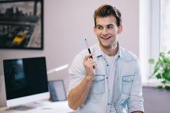 Mirada de los hombres sonrientes en la oficina Diseñador elegante en el trabajo El trabajador consiguió idea imagen de archivo