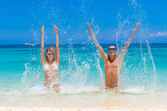 Mirada de los pares de la playa Pares jovenes felices que mienten en la arena debajo del sol Foto de archivo