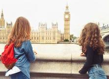 Mirada de moda de dos adolescentes en Big Ben, Londres fotos de archivo libres de regalías