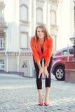 Mirada de moda, modelo caliente del día de una mujer joven que camina en la ciudad, llevando una chaqueta roja y pantalones negro Foto de archivo