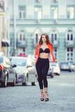 Mirada de moda, modelo caliente del día de una mujer joven que camina en la ciudad, llevando una chaqueta roja y pantalones negro Imágenes de archivo libres de regalías