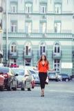 Mirada de moda, modelo caliente del día de una mujer joven que camina en la ciudad, llevando una chaqueta roja y pantalones negro Fotografía de archivo libre de regalías