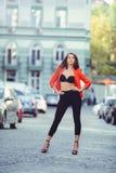 Mirada de moda, modelo caliente del día de una mujer joven que camina en la ciudad, llevando una chaqueta roja y pantalones negro Foto de archivo libre de regalías