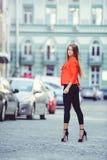 Mirada de moda, modelo caliente del día de una mujer joven que camina en la ciudad, llevando una chaqueta roja y pantalones negro Fotos de archivo libres de regalías