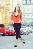 Mirada de moda, modelo caliente del día de una mujer joven que camina en la ciudad, llevando una chaqueta roja y pantalones negro Fotos de archivo