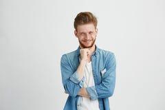 Mirada de pensamiento difícil astuta del hombre joven en lado con la mano en la barbilla sobre el fondo blanco Foto de archivo libre de regalías