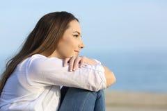 Mirada de pensamiento de la mujer relajada lejos en la playa Foto de archivo