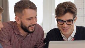 Mirada de tres hombres en el ordenador portátil metrajes