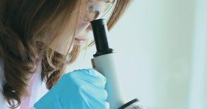 Mirada del científico a través del microscopio para el experimento almacen de video