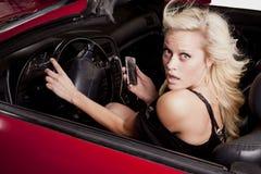 Mirada del coche del teléfono de la mujer Imagenes de archivo