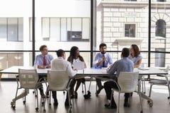 Mirada del equipo del negocio al encargado en la reunión en oficina abierta del plan fotografía de archivo libre de regalías
