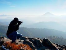 Mirada del fotógrafo abajo en el valle de la persona chapada a la antigua El hombre se está arrodillando en el acantilado y toma  Fotos de archivo