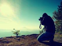 Mirada del fotógrafo abajo en el valle de la persona chapada a la antigua El hombre se está arrodillando en el acantilado y toma  Fotografía de archivo libre de regalías