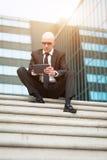 Mirada del hombre de negocios confiada usando la tableta del ordenador Imágenes de archivo libres de regalías
