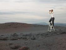Mirada del hombre de negocios lejos para las nuevas oportunidades de negocio con un telescopio imágenes de archivo libres de regalías