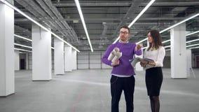 Mirada del hombre y de la mujer en los documentos mientras que discute proyecto arquitectónico almacen de metraje de vídeo