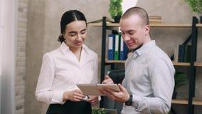 Mirada del hombre y de la mujer en la pantalla de la discusión de la tableta y de la ventaja metrajes