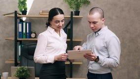 Mirada del hombre y de la mujer en la pantalla de la discusi?n de la tableta y de la ventaja