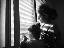 Mirada del muchacho y de la madre a través de la ventana fotos de archivo libres de regalías