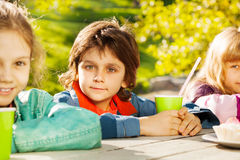 Mirada del muchacho y de muchachas con sentarse verde de las tazas Imagen de archivo libre de regalías