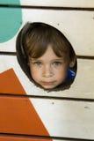 Mirada del niño pequeño detrás de la cerca de madera Foto de archivo