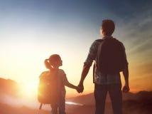 Mirada del niño y del papá en la puesta del sol Foto de archivo