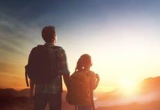Mirada del niño y del papá en la puesta del sol Foto de archivo libre de regalías