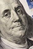Mirada del ` s de Benjamin Franklin en cientos billetes de dólar r imagen de archivo