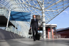 Mirada del trabajo del viaje del hombre de negocios el tablero de la muestra que camina con la carretilla del equipaje Fotos de archivo libres de regalías