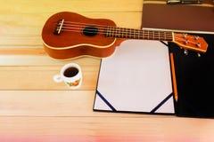 (Mirada del vintage y del instagram) del ukelele clásico con A4 en blanco ningún Foto de archivo libre de regalías