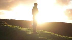 Mirada distante en el hombre que mira fijamente en la puesta del sol almacen de video