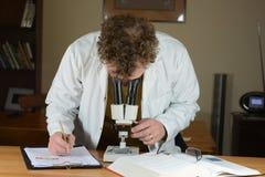 Mirada en el microscopio - primer Fotografía de archivo libre de regalías