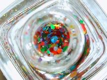 Mirada en esmalte de uñas con brillo colorido del hexágono Foto de archivo libre de regalías