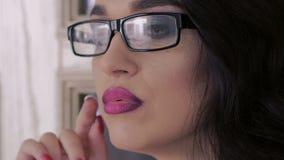 Mirada en la cámara de la mujer en vidrios lentamente almacen de video