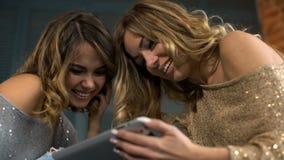Mirada feliz de la mujer joven dos en la tableta y la risa almacen de metraje de vídeo
