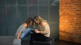 Mirada feliz de la mujer joven dos en la tableta y la risa metrajes