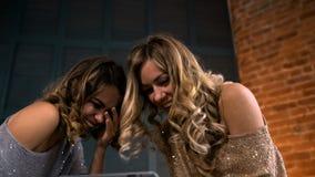 Mirada feliz de la mujer joven dos en la tableta y la risa a cámara lenta almacen de video