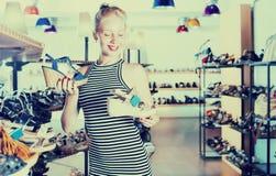Mirada femenina joven alegre a partir de dos pares de sandalias Fotografía de archivo libre de regalías
