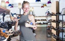 Mirada femenina joven alegre a partir de dos pares de sandalias Imagen de archivo libre de regalías