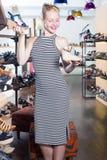 Mirada femenina joven alegre a partir de dos pares de zapatos Fotografía de archivo libre de regalías