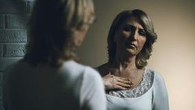 Mirada femenina mayor triste en espejo con el repugnancia, problema de envejecimiento, inseguridades almacen de metraje de vídeo