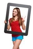Mirada femenina a través del marco que da el pulgar para arriba Foto de archivo libre de regalías