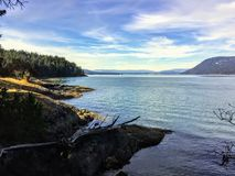 Mirada hacia fuera de las orillas de la isla de Portland a través del océano tranquilo hermoso a la isla de Saltspring imágenes de archivo libres de regalías