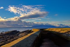 Mirada hacia fuera del puerto de Saltcoats a Arran como el sol refleja en la pared del puerto fotografía de archivo libre de regalías
