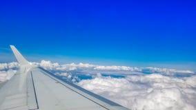Mirada hacia fuera a trav?s de una ventana de la porta de los aeroplanos durante un vuelo fotografía de archivo