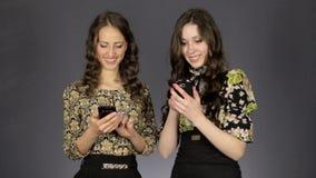Mirada hermosa de dos muchachas en la pantalla del teléfono almacen de metraje de vídeo