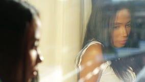 Mirada hermosa deprimida de la mujer fuera de la ventana almacen de metraje de vídeo