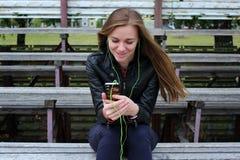 Mirada hermosa joven de la muchacha y música que escucha en su teléfono móvil que los estadios viejos bench Foto de archivo