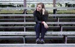 Mirada hermosa joven de la muchacha y música que escucha en su teléfono móvil que los estadios viejos bench Imagen de archivo libre de regalías