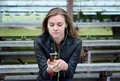 Mirada hermosa joven de la muchacha y música que escucha en su teléfono móvil que los estadios viejos bench Imágenes de archivo libres de regalías